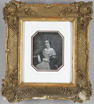 Junge Frau mit einem umgehängten Schal an einem Tisch sitzend.