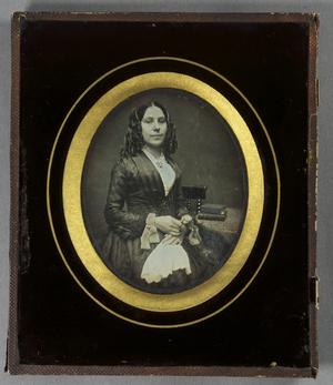 Junge Frau, seitlich am Tisch mit Büchern sitzend, mit einem Tuch in der Hand, Halbfigur, teilkoloriert.