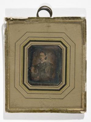 Portrett av ukjent kvinne sittende med den ene armen hvilende på et bord. Portrait of unknown woman seated with one arm resting on a table.