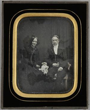 Ehepaar sitzend, die Frau mit einem weißen Tuch in der Hand, Ganzfigur.