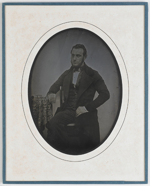 Portrait of a man posing with parts of a clock, watchmaker