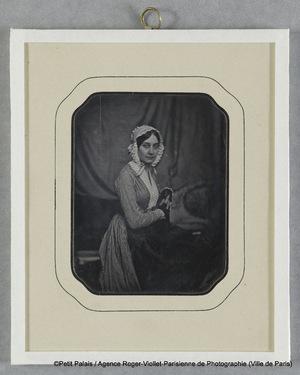Madame Riesener avec coiffe blanche et robe à carreaux