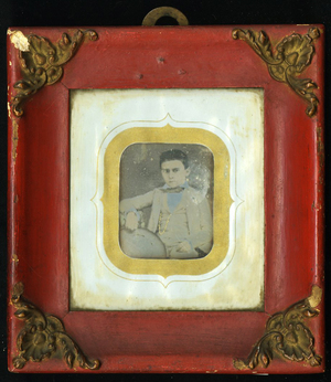 Half length frontal portrait of seated boy holding a hat. He wears a light color suit, the chain of his pocket watch is colored in gold. On the back of the frame, newspaper was used to seal the back before applying the finishing paper.