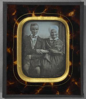 Älteres Ehepaar, sitzend, die Frau mit einer weißen Haube und einem umgehängten gemusterten Schultertuch, hat eine Hand um die Schulter ihres Mannes gelegt. Er hält ihre andere Hand fest.
