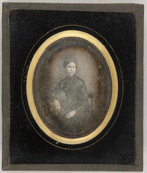 Junge Frau in schwarzem Kleid auf einem Stuhl am Tisch sitzend, ein Arm darauf ruhend.