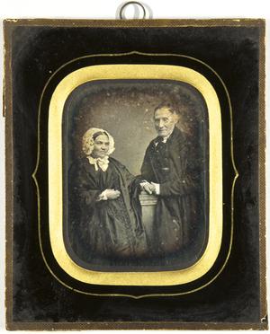Älteres Ehepaar, die Frau mit weißer Haube sitzend, der Mann neben ihr stehend ihre Hand haltend, Dreiviertel.