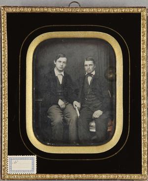 Zwei junge Männer, sitzend, einer hält ein Buch in der Hand, Ganzfigur.