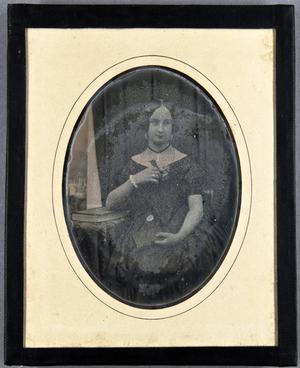 Junge Frau mit einem Buch in einer Hand und einer Rose in der anderen, an einem Tisch sitzend, auf dem ein großes Buch liegt. Im Hintergrund ein Vorhang, der links die Ansicht auf eine Burg oder ähnlichem frei gibt.