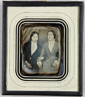 Zwei Frauen sitzend, eine hakt sich bei der anderen unter, evtl. Schwestern