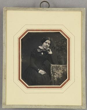 Junge Frau am Tisch mit einem Blumenkorb sitzend, Dreiviertel.