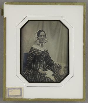 Frau mit weißer Haube und in gemustertem Kleid mit einem Tuch in der Hand, am Tisch sitzend.