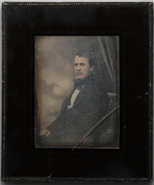 Half length portrait of a seated man (Leopold Krohn) with sideburns, posed sideways onto the camera with his head turned towards the camera. He wears dark jacket and trousers, waistcoat, a white shirt with high collar and dark cravat. He sits on a upholstered chair with carved armrest. His left hand is inside the jacket, right fist is closed and rests on his thigh. There is a painted sky background and a curtain.