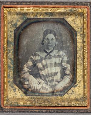 Puolikuvassa nuori nainen ruudullisessa mekossa, vyötärö istuva, kaulassa tumma koristenauha. Vasen käsi nojaa pöydän reunaan, käden alla on kirja. Vasemmassa etusormessa oleva sormus on kullan värinen.
