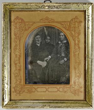Älterer Mann mit Kappe und seiner Tochter, die ihre Hand auf seinen Arm gelegt hat, und seinem Sohn, der hinter ihm zwischen den beiden sitzenden steht. Ganzfigur.