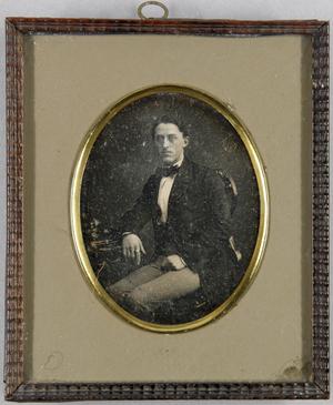 Junger Mann seitlich an einem Tisch sitzend, trägt einen Ring am Zeigefinger.