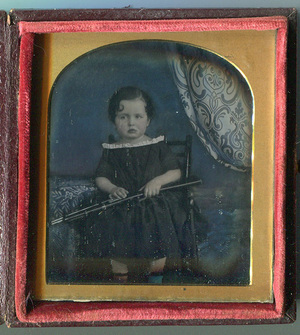 Portrait of seated child with a toy rifle.