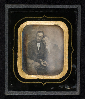 Portrait of a man and a boy, half figure, seated. The man is holding his arm around the boy and holding his hand. This is an unusual portrait as so much feelings between a father and his son is expressed.