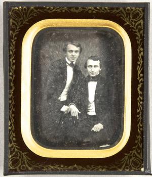 Zwei junge Männer, einer sitzend, der andere leicht zu ihm gebeugt.