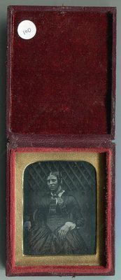 Portrait taken out of doors. Plate unsealed, shows heavy tarnish and has vertical polishing lines.
