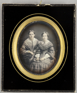 Zwei junge Damen am Tisch sitzend, Dreiviertel, koloriert.