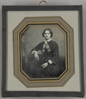 Junge Frau mit karierter Halsschleife, sitzend, Dreivertel.