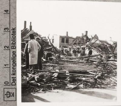 Folk ser på ruiner af bombede boliger