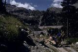 Alpinistes vora les vies i una vagoneta de la Mesilla, al fons la resclosa de la Restanca