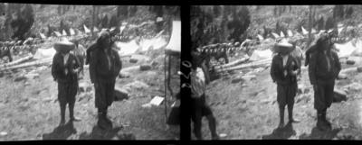 Campament a la muntanya amb dos caçadors i excursionistes al davant