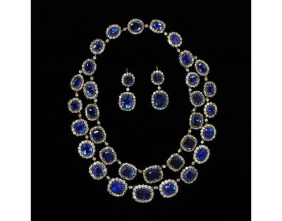 Necklace, sapphires in brilliant-cut diamond borders, open-set in silver, England, about 1850.Necklace, sapphires in brilliant-cut diamond borders, open-set in silver, backed with gold, in two rows and graduated. Adapted in the 1930s from a single row necklace to a double row, probably for Lady Cory; the earrings possibly made from parts of the necklace.Sapphires, diamonds, silver and gold.