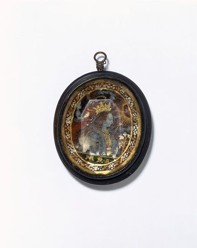 Horn ,with a verre eglomisé plaque behind glass, Salzburg, ca.1650-1700. Double-sided pendant made of horn. Set in the front behind glass is a verre eglomisé (reverse painted glass) plaque, depicting the Virgin Mary. Set into the back are small relics and pieces of paschal candle, labelled Santa Martyr (martyr saint) and Agnus Dei (lamb of God).  Horn ,with a verre eglomisé plaque behind glass.