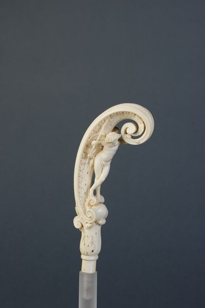 Parasol handle of carved ivory, the figure of Cupid under the curved handle of acanthus leaf design, signed and dated by Jean Norest, France, 1859. Carved ivory parasol handle, with an acanthus leaf design containing under the curve of the handle a standing Cupid holding a bow. From a short circular stem, crowned with an irregular capital formed of acanthus leaves and a volute, rises a scroll carved on the whole length inside with an acanthus leaf; within stands a nude cupid on a short scroll rising from the base of the larger one, he holds a bow in his right hand and supports himself by leaning on the upper extremity of the larger scroll with his left hand which holds an arrow.  Ivory, carved.