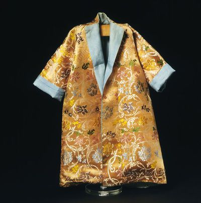 Doll's undress gown of silk, London, 1690-1700. Doll's undress gown of a kimono-style in salmon pink silk with a floral pattern in purple, pale blue, emerald green, lime green, orange and deep pink. It is lined with a figured blue Chinese export silk, which forms the cuffs and robings.
