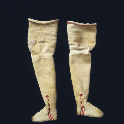 Pair of doll's silk stockings, London, 1690-1700. Pair of doll's stockings of hand-knitted ivory silk reaching to mid-thigh, with a red band at the top and a red clock on each side of the ankles.;;