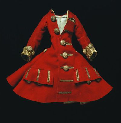 Doll's coat of wool lined with silk, London, 1690-1700. Doll's coat of red wool with full skirt, lined with pale blue spotted silk. The cuffs are of silver tissue trimmed and fastened with silver thread passementerie buttons. There are seven buttons down the front, three under each pocket, three on each sleeve cuff and one over each skirt gather on the hip. There are two horizontal pockets on the front, lined with pale blue spotted silk.