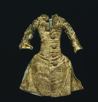 Doll's waistcoat of silver tissue, London, 1690-1700. Doll's waistcoat of silver tissue with sleeves, with a semi-naturalistic floral pattern of plain silver thread on white silk taffeta. The waistcoat is lined with light blue spotted silk and has worked silver thread buttons.