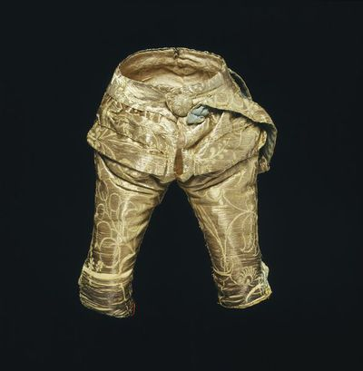 Doll's breeches of silver tissue, London, 1690-1700. Doll's breeches of silver tissue in a semi-naturalistic floral pattern carried out in paired shoots of plain silver thread on a white silk tabby ground. They have a fly front and a flapped horizontal pocket at each hip, lined with chamois leather, the flaps are faced with silk. To the left side is stitched the sword hanger, of the same silver tissue, lined with blue spotted silk. The breeches are lined with white flannel.