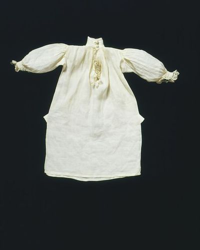 Doll's shirt of linen trimmed with bobbin lace, London, 1690-1700. Doll's shirt made of fine linen of knee length with side slits. The neck opening and cuffs are trimmed with English bobbin lace. The band collar and cuffs fasten with a darned white thread button. The cuffs and shoulders are embroidered with French knots in white thread.