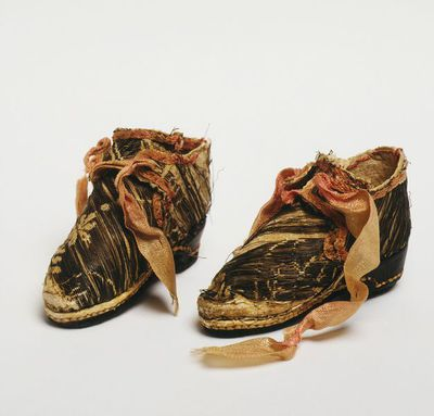 Pair of doll's shoes of leather and brocaded silk, London, 1690-1700. Pair of doll's shoes, made of silver brocaded white silk, faced and with a fastening of pink silk ribbon. The soles are brown leather with a white leather rand.;;
