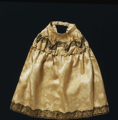 Doll's petticoat of silk damask trimmed with bobbin lace, London, 1690-1700. Doll's petticoat of ivory Chinese export silk damask gathered at the waist with a gathered hip yoke. The hip to hem flounce is headed and trimmed top and bottom with silver-gilt bobbin lace.  It is faced at the waist with silk ribbon, now fastened with a pin and the hem is faced with ivory silk taffeta.