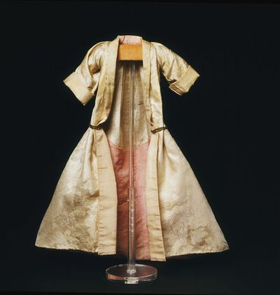 Doll's mantua of silk damask lined with silk taffeta, London 1690-1700. Doll's mantua of ivory Chinese export silk damask with a train at the back. The train is lined and faced with self-patterned pink silk taffeta with a self-coloured woven pattern which also forms the robing and turn back cuffs. The mantua is T-shaped with a sack back and a gore from the waist to hem at each side. The mantua has a double box pleat at the back and wide three-quarter length sleeves. A cord of metal braid stitched inside the waist, attached to a gilt thread metal button attached to each hip holds the mantua open over the petticoat.