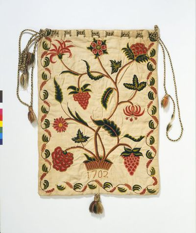 Embroidered workbag in crewel wool on a linen and cotton ground, England, dated 1701 and 1702. Rectangular workbag embroidered in crewel wools in chain stitch on a plain woven linen and cotton ground. Using the full width of the material, it was worked as one long piece then side-seamed by butting and oversewing the selvedges. There is a contemporary linen lining. The embroidered design depicts on one side a central two-handled vase containing meandering stems with large-headed blooms (a carnation and other multi-petalled flowers) in shades of pink, red and brown. The stems and leaves are worked in shades of green and brown. This face of the bag is initialled 'ER.' on either side of the vase and dated '1701'. Two exotic birds are embroidered on either side of the vase and there is a border design on three sides of both front and back showing meandering flowers and leaves in shades of pink, brown, yellow and green. The other side, the back, has a similar floral design to the front, growing out of a shaded hillock. It is dated '1702'. The bag is fastened by means of a drawstring of plaited linen and wools in green and fawn which runs through eyelet slits blanket stitched in green wool. The drawstring is decorated with three tassels made with linen heads decorated and fringed with natural linen and the same coloured wools used in the decorative embroidery. The bottom of the bag is decorated with a larger tassel.  Embroidered in crewel wool on a linen and cotton ground.