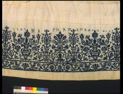 Linen skirt dress embroidered in silk, made by Maria Papadopoula, Crete, Greece, 1757. Linen skirt dress with a floral border embroidered in blue silk. The name of the embroiderer 'Maria Papadopoula' and the date '1757' are included in the border. A tuck has been put into the garment to shorten it, so it is now skirt length. The shoulder straps are still attached and the bust is gathered. In Cretan feather, fishbone, satin, chain, back, double running and whipped stitches and French knots. Frieze of alternating vases of flowers. Made up of five loom widths of linen and cotton.  Linen and cotton embroidered with silk.