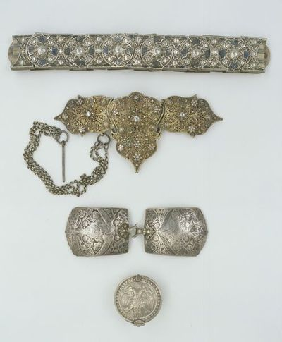 Belt of inter-locking silver slides, with niello decoration, on a band of cloth, Cyprus, 18th century.Belt of interlocking silver and niello slides on a band of cotton woven in blue and white stripes. There are 13 slides with circular fronts and 13 shaped like a diabolo which fit between the circles. Each piece has a copper alloy bar at the back, so that they can be threaded on the belt. The fronts are decorated with cast stars, rosettes and tulips, picked out in niello. There is a loop soldered to the last slide at one end of the belt, and a sideways hook at the other, to fasten it, which may have been replaced.Silver and niello, with copper alloy bars, on a belt of blue and white striped cotton.