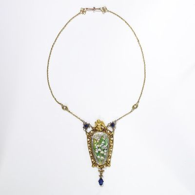 Gold necklace with enamelled pendant, pearls and sapphires, probably designed and made by Nelson Ethelred Dawson, with enamel panel by Edith Dawson, London, about 1900.Gold chain necklace with pendant, which is surmounted by a cast cherub and set with a painted enamel plaque with lilies-of-the-valley surrounded by pearls in openwork; the drop set with a sapphire; sapphires and pearls on the chain. The enamelled plaque a shaped oval, decorated with a spray of lilies of the valley, the leaves translucent over foil. The enamel held by four claws in the pierced gold frame which is in the form of a cartouche with stepped edges shaped to receive the console terminals of the claws; a scrolling band of pierced openwork is set with pearls and the pendant is surmounted by a winged cherub. A faceted sapphire in an open gold collet forms the tail of a pendant below a gold fleur-de-lis. Two faceted sapphires, each in an open collet with wire petals form the attachments connecting pendant and chain. The chain of single links, is decorated with two pearls, each in a chased frame formed of two leaves placed asymmetrically, and terminates in a clasp shaped as two openwork wire florets with pellets attached, connected by an S-shaped clasp of a differently coloured gold from the rest.Gold, enamel, pearls and sapphires.