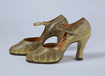 Pair of ladies' snake skin shoes, Great Britain, ca. 1928. Pair of ladies' shoes made from natural grey-yellow snake skin with a patterned white metal buckle passed through a loop to fasten. The shoes are lined with light tan leather, the toe with canvas. The shoes are stained yellow tan with '4' incised on the sole of the right shoe.Snake skin, metal buckle, lined with leather and canvas.