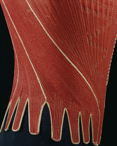 Red wool stays, back lacing, English 1770-1780. These back-lacing stays of red wool have a high narrow back with a wide curving decolletage and a point in front, about 5 cm below the waistline. The white lacing up the centre front is decorative. The centre front piece is very wide at the top and narrow at the bottom, causing the two side pieces on each side curve round from back to front. There are two back pieces on each side of the lacing, Below the waist there are 19 tabs. The stays are laced through 13 eyelets on each side arranged asymmetrically. The wool backed with either linen or canvas, and stitched with linen thread to form the compartments for strips of whalebone between 4 and 5 mm wide, running vertically and diagonally. The stays are lined with glazed linen and the edges bound with linen twill tape. Plain weave linen tape fastens the shoulders. White silk braid forms the decorative lacing at the front. White silk ribbon covers the seams. There is a centre busk of whalebone about 2 cm wide. Another 2cm strip of whalebone runs horizontally across the upper front edge. Whalebone strips of 1cm reinforce behind the seams. The shoulder straps, each with an eyelet, extend from the front and fasten with tape through an eyelet at each shoulder back.  Wool backed with linen or canvas, stitched with linen thread reinforced with strips of whalebone, lined with glazed linen, bound with linen twill tape, fastened with plain weave linen tapes and decorated with silk braid and silk ribbon.
