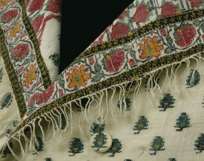 Man's waistcoat of cashmere wool and linen, fabric woven in India, 1775-1785, and made in Great Britain, 1785-1790.Man's waistcoat of cashmere wool and linen, and made from a fringed Indian cashmere shawl with a white ground. Patterned with alternating rows of small green pines with yellow centres. The borders are composed of alternating rose pink carnations and yellow flowers, with a green centre linked by their stems that form an arcaded pattern, and edged with black interwoven with small yellow gold leaf shapes. A portion of the ends of the shawl, now used to face the lapels, has a design of large rounded motifs filled with a close pattern of pinks linked by their foliage and narrow black stripes. The body of the waistcoat is made from the main ground of the shawl. The woven borders are stitched around the edges, and the sides of the ends with borders and fringe attached face back the lapels. The waistcoat is just over waist-length, square cut, double-breasted, and cut to allow the lapels to fall open. There are plain welted bands stitched at pocket level but no pockets have been inserted and it is double-breasted. There are 24 small round buttons covered with material from the body of the shawl. The back is made from white linen.Cashmere wool and linen, hand woven and hand sewn.