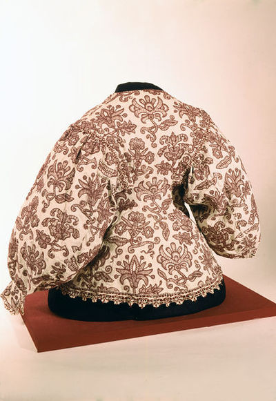 Woman's waistcoat, 1630s, English; Linen embroidered with red wool crewelwork, bobbin lace trimming.