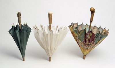 Printed silk parasol, Belgium, ca. 1925. The cover is made from tussore silk with an oriental carpet like printed pattern in orange, brown, green and yellow. When open, it is almost flat. The stick is light wood and short, with an inclined, expanded carved rough wooden knob. The tip is of matching wood. The ribs are of rectangular, hollow section white metal, and have grey tips. A ruche of the cover material is stretched between the stays and slider which is made from shiny white metal. There are two incised brass metal catches.Printed tussore silk on metal frame with wooden handle.