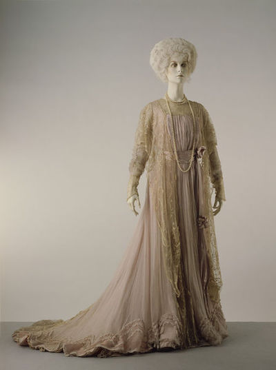Satin tea gown, probably designed by Worth, Paris, ca. 1900.Satin tea gown with two delicate overlayers of pink chiffon crêpe continuing over the train. The bodice is pouched into a broad satin belt with a falling sash. The gown is machine-stitched with hand-finished. Lined with two bones which fastens at the centre front and the bodice wraps over to fasten along the left side, all with hooks and eyes. Ecru tambour embroidered net draped over the shoulders. Low neck and trimmed with an insertion of the lace, as are the cuffs of the long gauge chiffon sleeves.Satin, chiffon crêpe with ecru tamboured net, lace, lined, boned.
